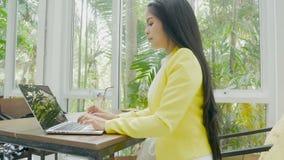 4k lengte het bedrijfsvrouw typen op een laptop toetsenbord bij koffiewinkel stock video