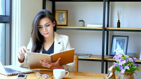 4K lengte, mooie Aziatische bedrijfsvrouwenzitting voor computerlaptop, lezing en tik over de pagina van het notaboek stock footage