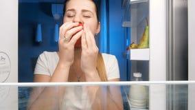 4k lengte van het jonge hongerige vrouw kijken in ijskast en het eten van rode appel stock videobeelden