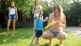 4k lengte van het leuke het lachen peuterjongen spelen met het water geven van tuinslang op gazon bij binnenplaats stock video