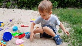 4k lengte van het leuke peuterjongen spelen in de zandbak op speelplaats bij park stock videobeelden