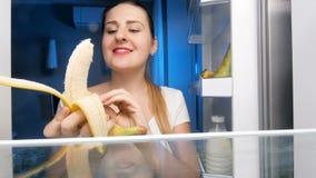 4k lengte van jonge glimlachende vrouw die banaan van ijskast, schil nemen en het bijten stock footage