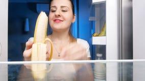 4k lengte van jonge hongerige vrouw schil en het eten van banaan bij nacht stock videobeelden