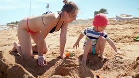 4k lengte van jonge moeder in bikini de bouwzandkasteel op het overzeese strand met haar 3 jaar oude zoon stock videobeelden