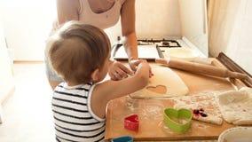 4k lengte van jonge moeder die haar weinig zoon onderwijzen scherp deeg voor koekjes met speciale plastic snijders stock footage