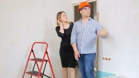 4k lengte van mannelijke contractant in bouwvakker die nieuw de bouwhuis tonen aan jonge onderneemster en het schudden van handen stock videobeelden