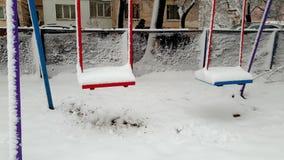 4k lengte van schommeling op speelplaats in sneeuw na blizzard bij de winter wordt behandeld die Geen jonge geitjes spelen rond stock footage