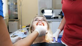 4k lengte van vrouwelijke patiënt met mond widener zitting als tandartsvoorzitter bij tandkliniek stock footage