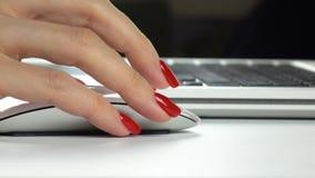 4k lengte Vrouwen` s hand met rode manicure die een draadloze computermuis met behulp van Close-up stock videobeelden