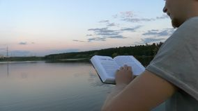 4k - Libro de lectura del hombre joven en el puente cerca del lago almacen de video