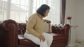Senior woman sitting on couch and massage her knee
