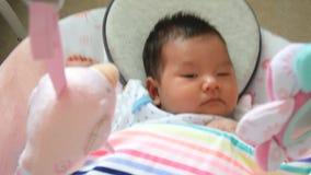 4K longueur, sensation asiatique adorable de bébé somnolente, se situant dans un berceau d'oscillation banque de vidéos