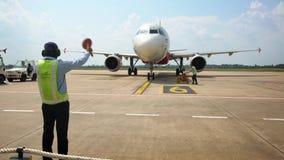 4K Lotniskowy pracownik sygnalizuje heblować pilota na pasie startowym przy Siem Przeprowadza żniwa Kambod?a zbiory