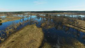 4K. Low flight and takeoff over flooded blue river in early spring, aerial panoramic view stock video footage
