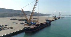 4K lucht videofilm van een containerschip vast in de haven van Bautino op de kusten van het Kaspische Overzees, Kazachstan stock videobeelden