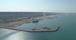 4K lucht videofilm van een containerschip vast in de haven van Bautino op de kusten van het Kaspische Overzees, Kazachstan stock video