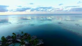 4k luchthommelcamera die omhoog in mooie warme oranje avondzonsondergang vliegen over het eiland kalm Vreedzaam oceaanzeegezicht  stock videobeelden