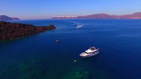 4K luchthommellengte van een duur jacht op het overzees Santorini stock footage