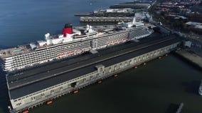4k luchthommelmening over de reuzeboot van het de cruiseschip van de toeristenluxe in diep blauw oceaanwater in de baai van de de stock footage