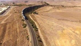 4k luchthommelschot van de moderne stedelijke bewegingen van de passagierstrein door reuze droge zandwoestijn in de heuvellandsch stock videobeelden