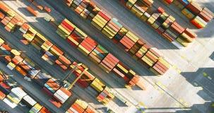 4K luchtmening die van havenkraan zich diagonaal boven kleurrijke containers in de haven bewegen