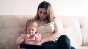4k: A mãe e a menina bonitos novas estão sentando-se no sofá e estão ensinando-se usando um tablet pc filme