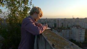 4k - Młody pisarz znajduje jego duma na dachu drapacz chmur przy zmierzchem zbiory
