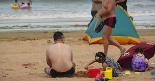 4k mała dziewczynka bawić się piasek na plaży, ojciec towarzyszył jej córki, Chiny zbiory