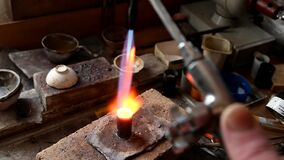 Adult Jeweler melts gold in liquid state for wedding ring. Craft jewelery