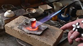 Caucasian jeweler melts gold in liquid state in crucible. Craft luxury jewelery