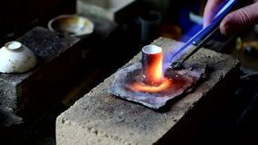 Jeweler melts gold in a liquid state in a crucible. Craft jewelery 4k footage