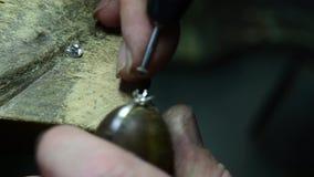 Jeweler puts diamond to golden wedding luxury ring. Craft jewelery