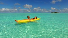 P02917 4k Maldives white sandy beach 2 people young couple man woman floating on airbed inflatable mattress swimming Stock Photos