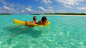 P02922 4k Maldives white sandy beach 2 people young couple man woman floating on airbed inflatable mattress swimming Stock Image