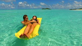 P02918 4k Maldives white sandy beach 2 people young couple man woman floating on airbed inflatable mattress swimming. 4k Maldives white sandy beach 2 people Stock Images