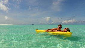 P02919 4k Maldives white sandy beach 2 people young couple man woman floating on airbed inflatable mattress swimming Stock Photography