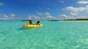 P02920 4k Maldives white sandy beach 2 people young couple man woman floating on airbed inflatable mattress swimming Royalty Free Stock Photos