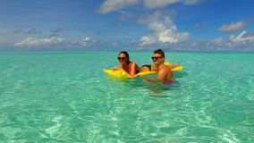 P02921 4k Maldives white sandy beach 2 people young couple man woman floating on airbed inflatable mattress swimming Royalty Free Stock Photo