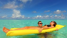 P02916 4k Maldives white sandy beach 2 people young couple man woman floating on airbed inflatable mattress swimming. 4k Maldives white sandy beach 2 people Royalty Free Stock Image