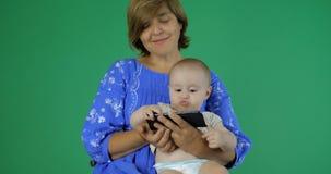 4k - A mamã e o bebê estão olhando algo engraçado em seu smartphone video estoque