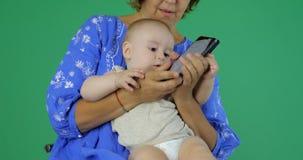 4k - A mamã inclina um telefone contra a orelha do bebê, movimento lento, chromakey filme