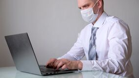 4k Man in medical mask and office clothes white shirt and tie talks business remotely from home on laptop. The call to