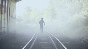 4K Man running away fast on foggy train tracks. Back view. Abstract background shot. Creative lifestyle runner shot. stock footage
