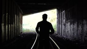 4K Lost man silhouette runs to dark tunnel exit. Back view. Abstract silhouette shot. Escape. Problems and depression.