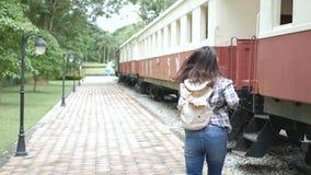 4K Mani d'ondeggiamento della donna turistica asiatica da dire arrivederci in treno di partenza alla stazione ferroviaria Arrived video d archivio