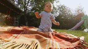 4K materiał filmowy śliczny chłopiec obsiadanie na koc przy ogródem zbiory wideo
