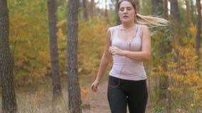 4k materiał filmowy bierze krótką przerwę młoda kobieta podczas gdy jogging przy lasem zbiory
