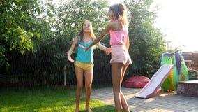 4k materiał filmowy dwa nastoletniej dziewczyny cieszy się deszcz na gorącym letnim dniu przy podwórkem zbiory
