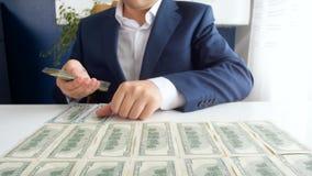 4k materiał filmowy kłaść dużą stertę USA dolary na biurowym biurku i liczy pomyślny biznesmen zdjęcie wideo