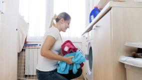 4k materiał filmowy piękny młodej kobiety brać czysty odziewa z pralki w pralni zdjęcie wideo
